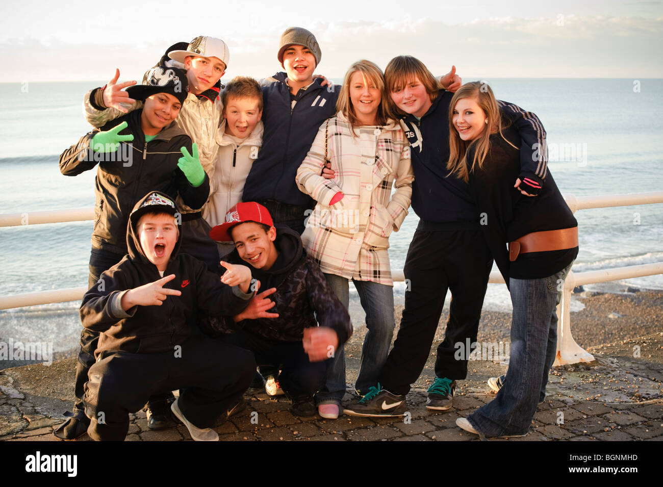 Group of  happy cheerful smiling teenage boys and girls together , winter afternoon, Aberystwyth Wales UK - Stock Image