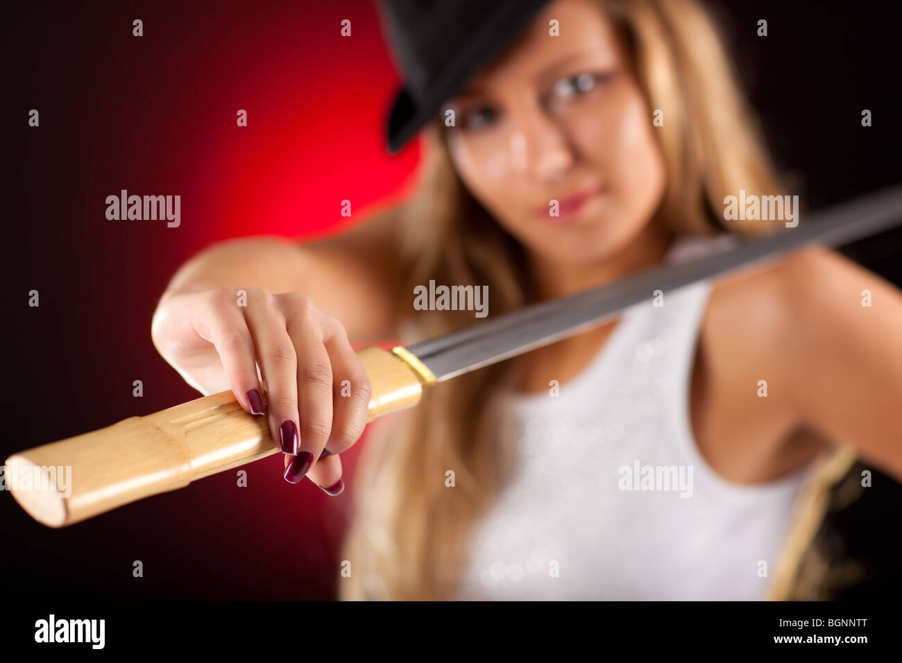 Strong fashion woman with hat and sword. Focus on hand.
