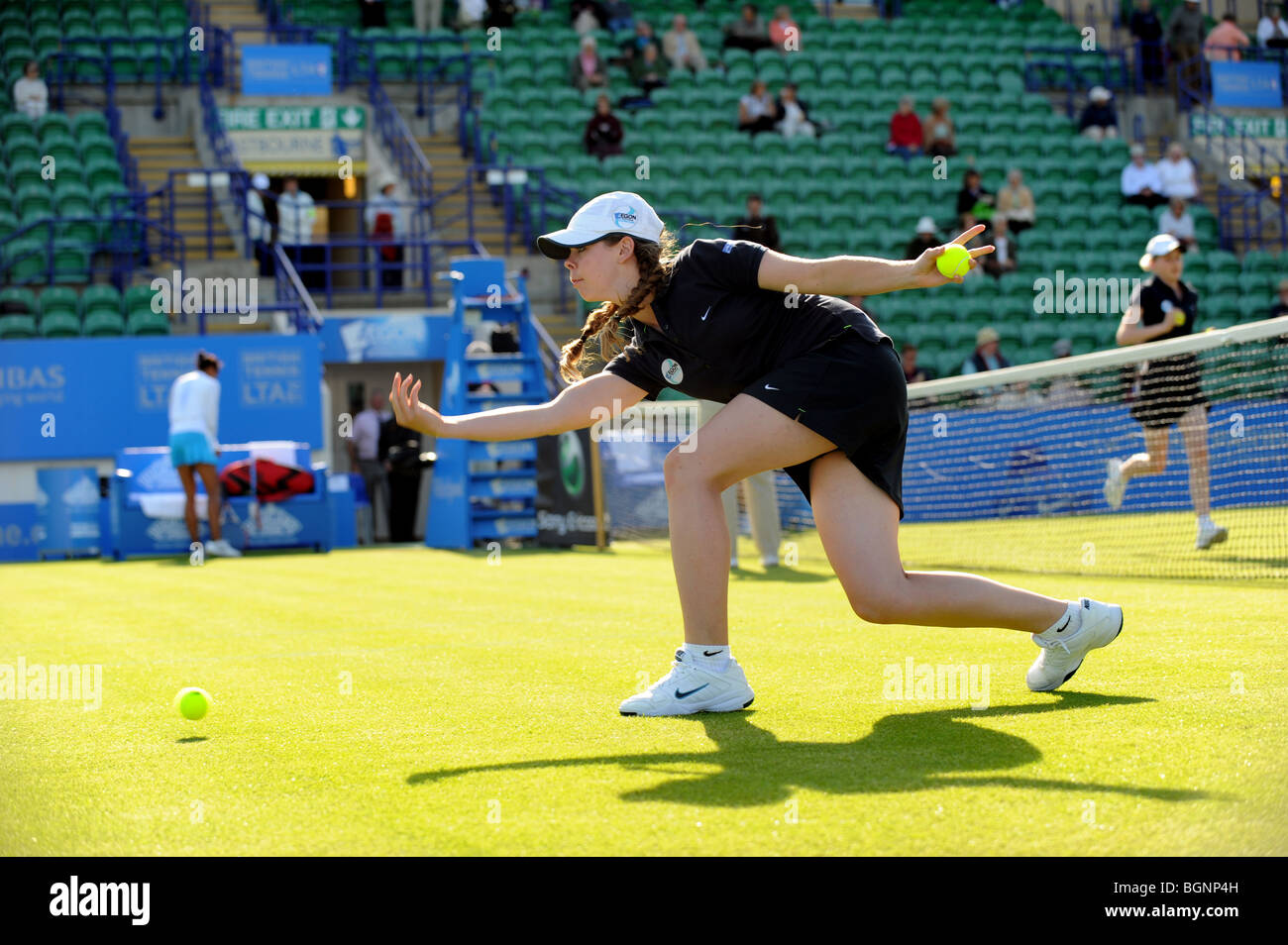 A ball girls throws balls up the court ready for the next match at the Aegon International 2009 Tennis Championships - Stock Image