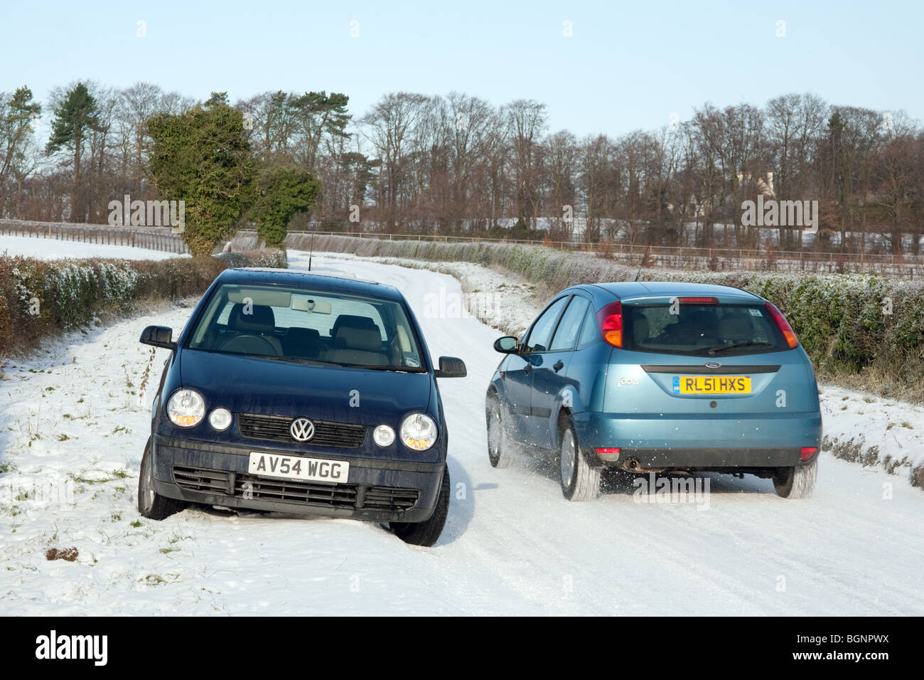 A car drives past a parked car in snow on a country road, Newmarket Suffolk, UK - Stock Image