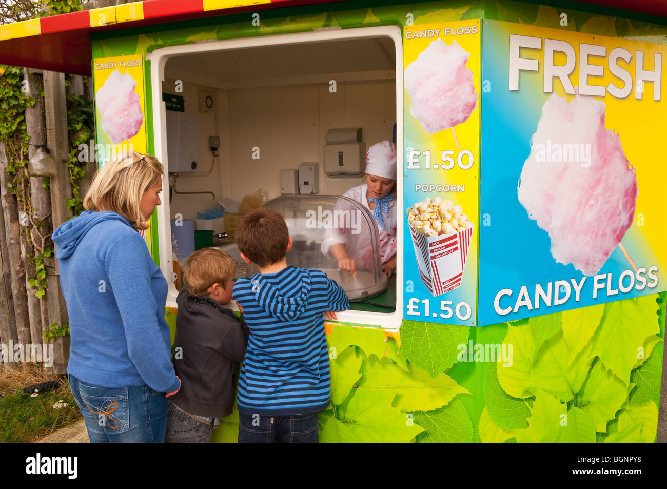 A mother buying candy floss for her children at a Uk stall - Stock Image