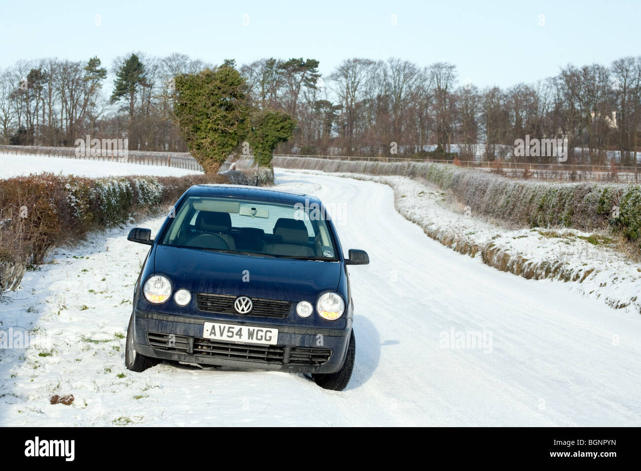 A car parked on the edge of a snow covered road, Newmarket Suffolk, UK - Stock Image