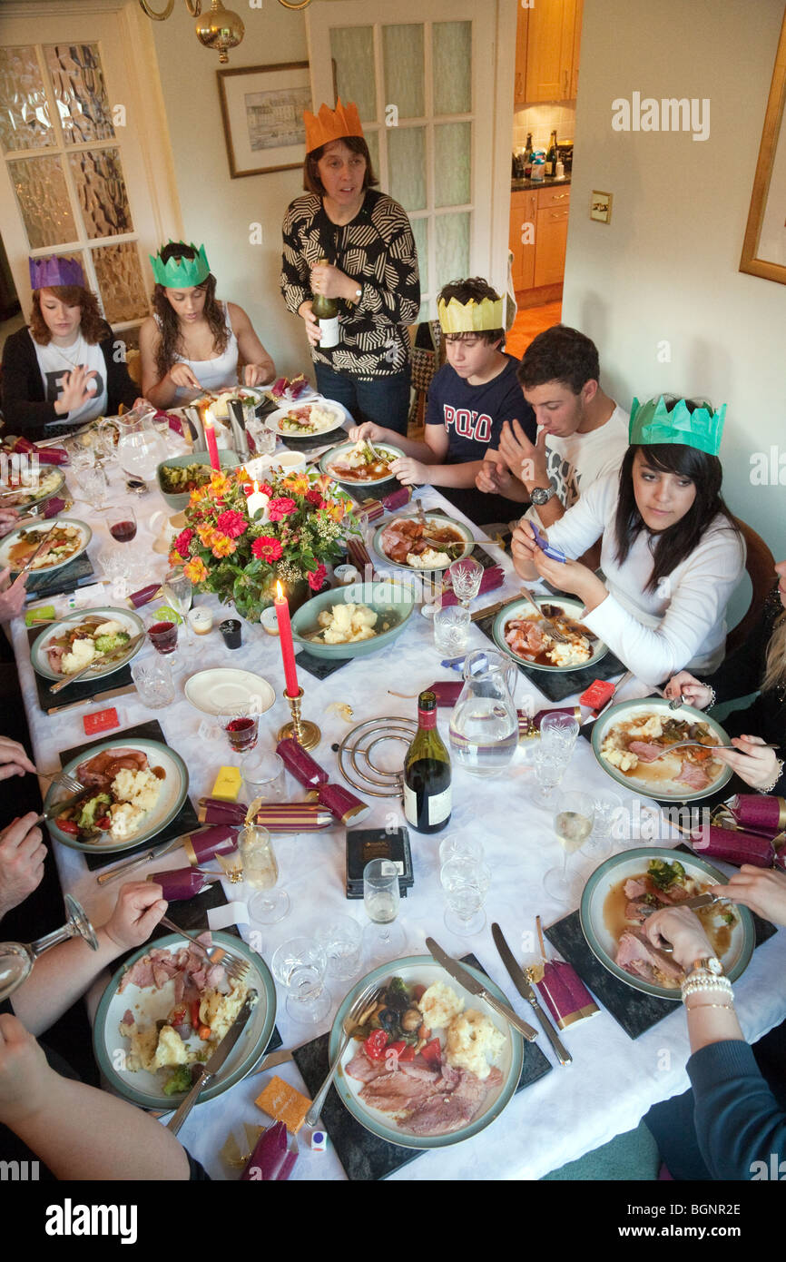 family and friends at a christmas dinner party on xmas day in the uk
