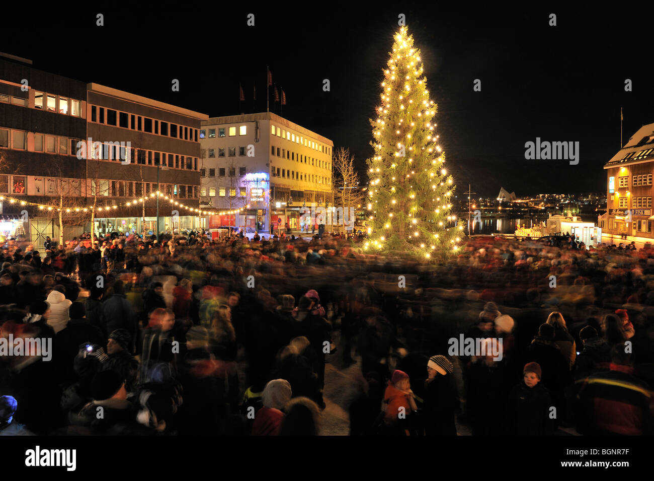 People walking around a Christmas tree in the city square in Tromso, North Norway - Stock Image