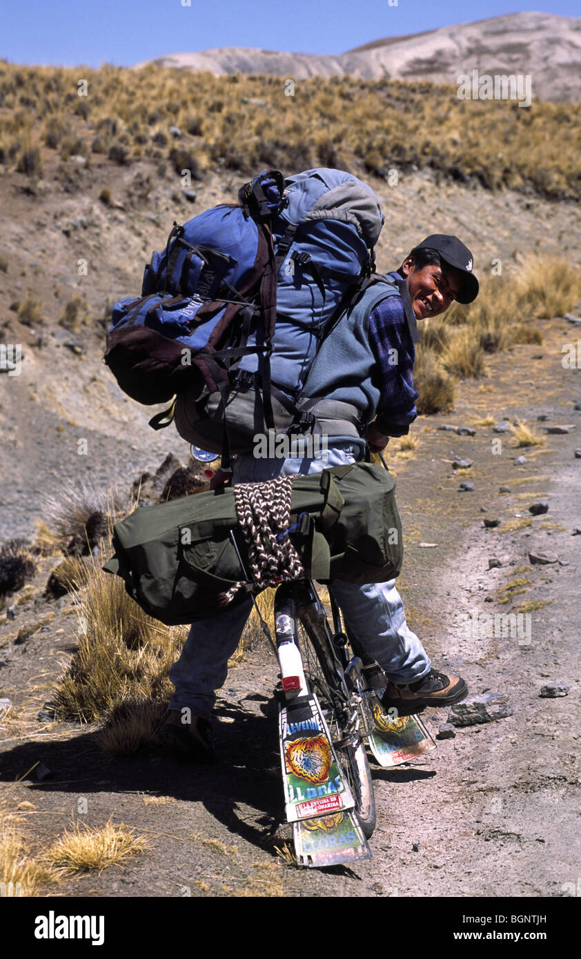 Local on a bike bringing equipment to a climbing expedition. Cordillera real, Bolivia. - Stock Image