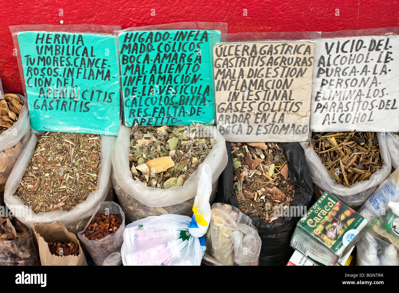 sacks of rather ugly herbal remedies for ailments including colitis alcohol parasites displayed in open containers - Stock Image