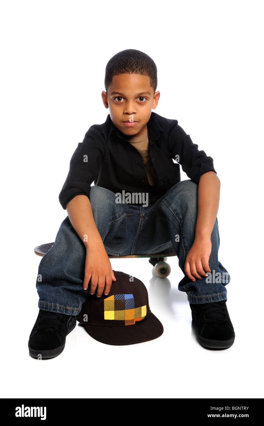 Young African American boy sitting on skateboard isolated over white - Stock Image