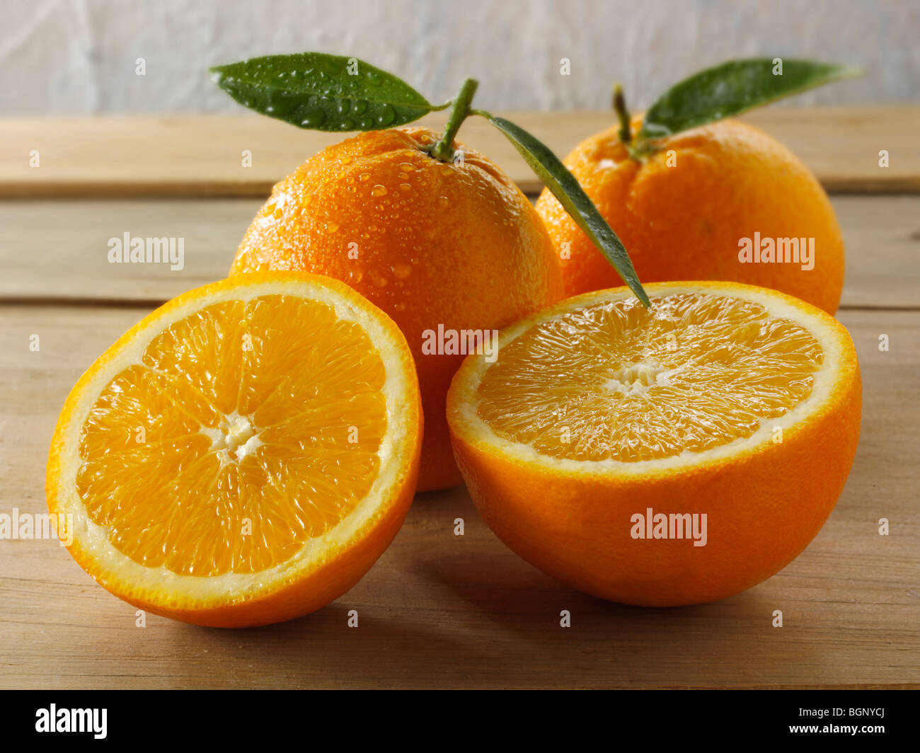 Whole and cut fresh oranges with leaves - Stock Image