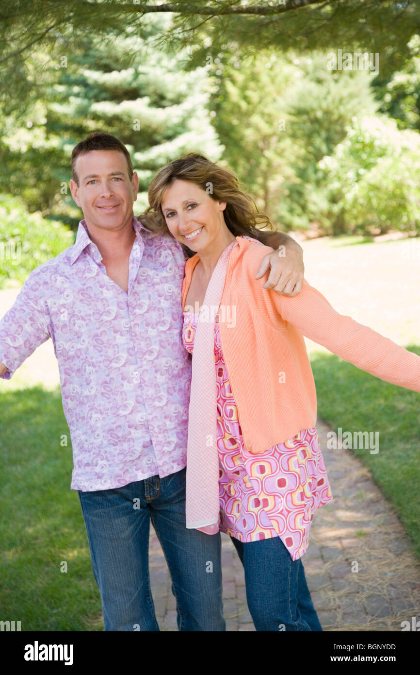 Portrait of a mature couple standing with their arm around and smiling - Stock Image