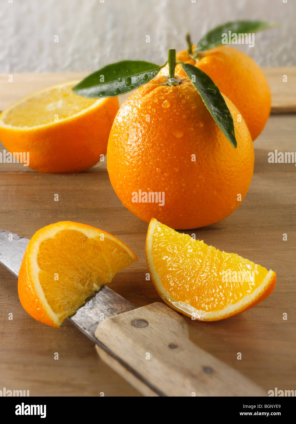 Whole and cut fresh oranges  with leaves in a kitchen - Stock Image