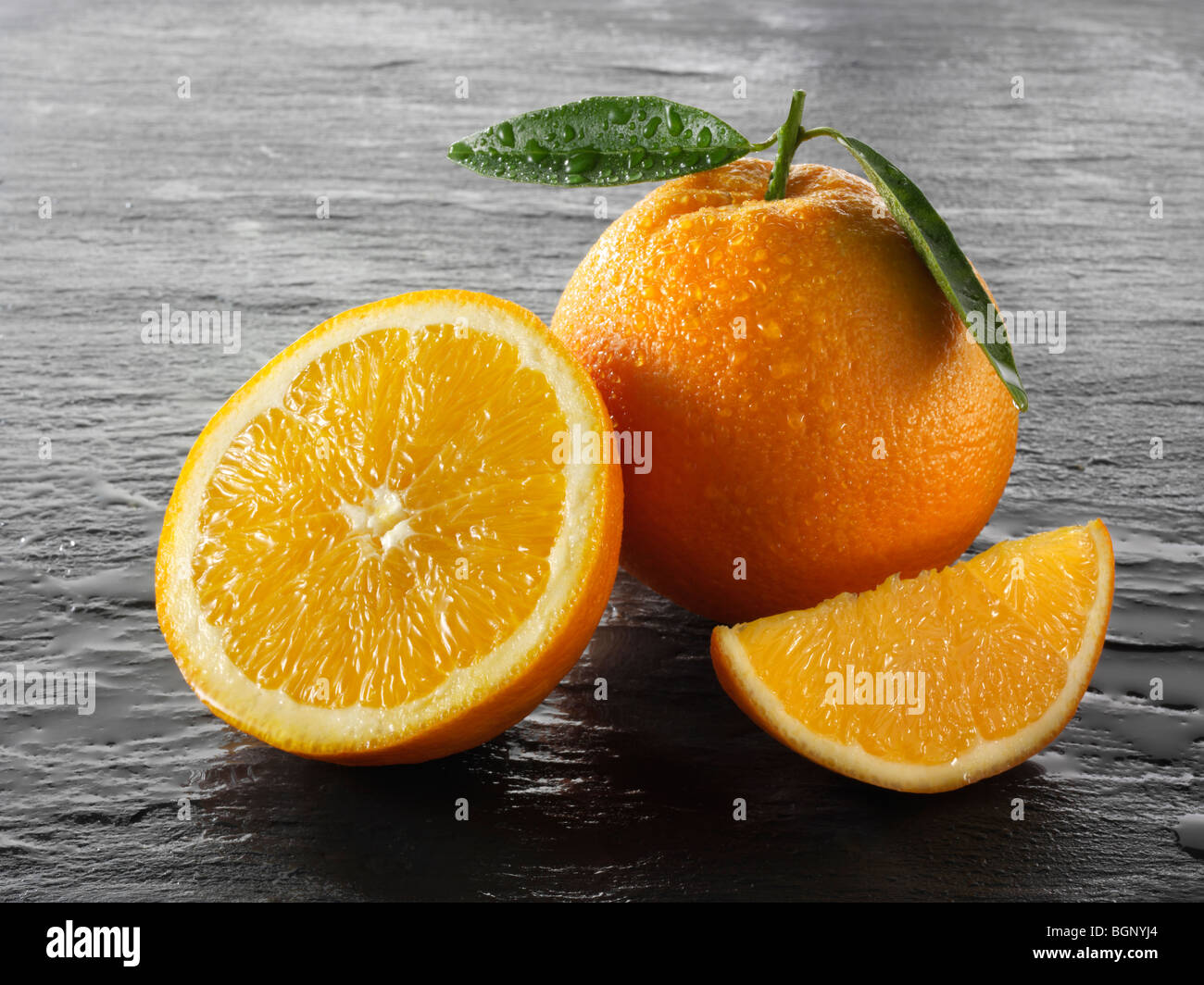 Whole and cut fresh oranges with leaves against a black background - Stock Image