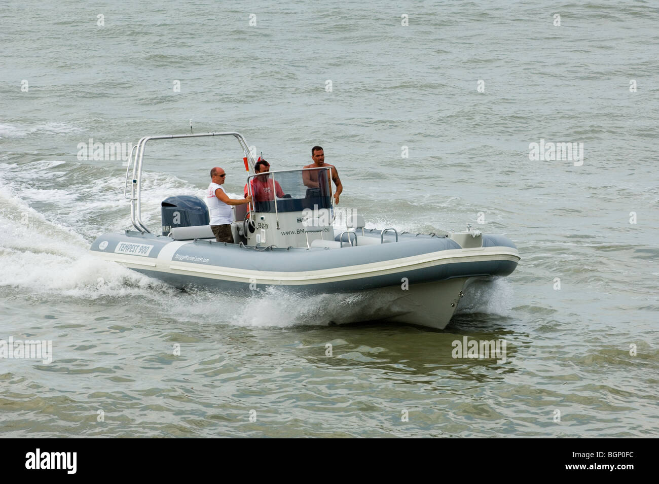 Three men riding powerboat on the North Sea, Belgium - Stock Image