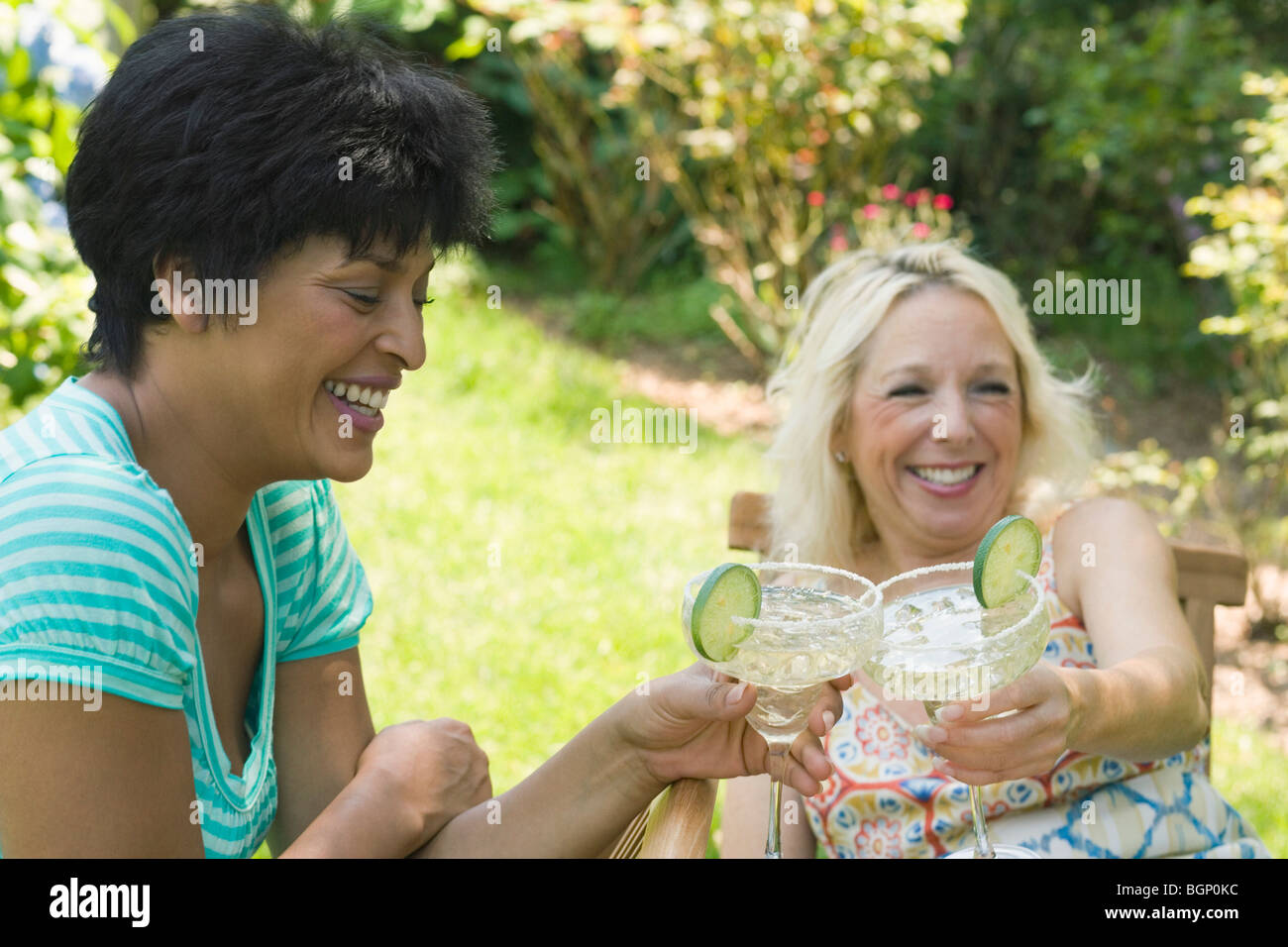 Two mature women toasting with martini glasses - Stock Image