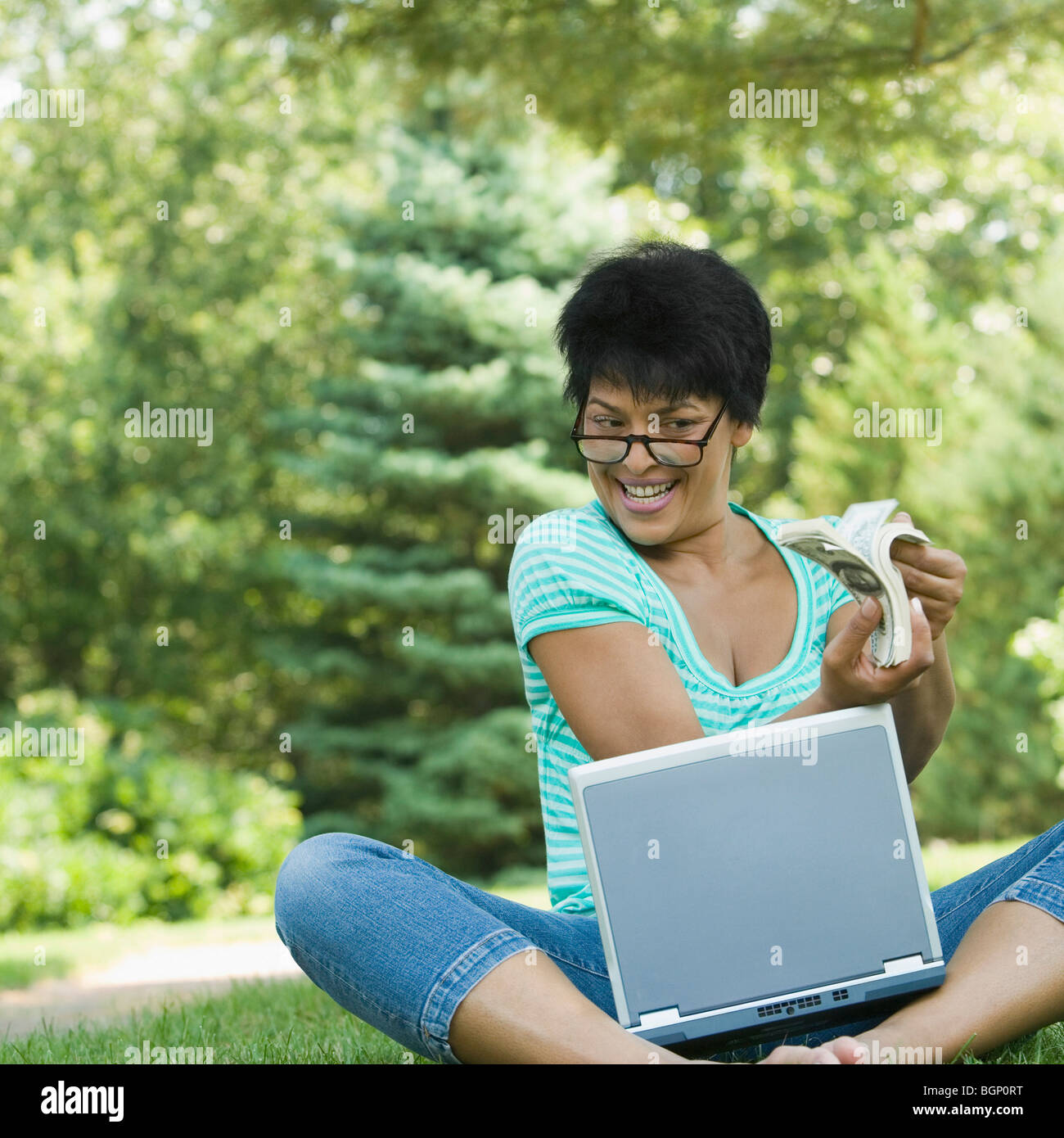 Mature woman sitting with a laptop and holding a wad of currency - Stock Image
