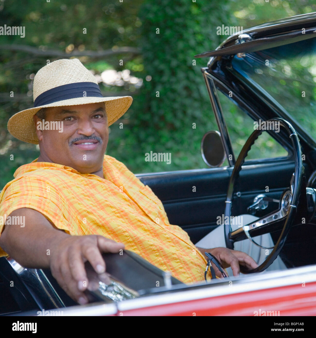 Portrait of a senior man sitting in a convertible car and smiling - Stock Image
