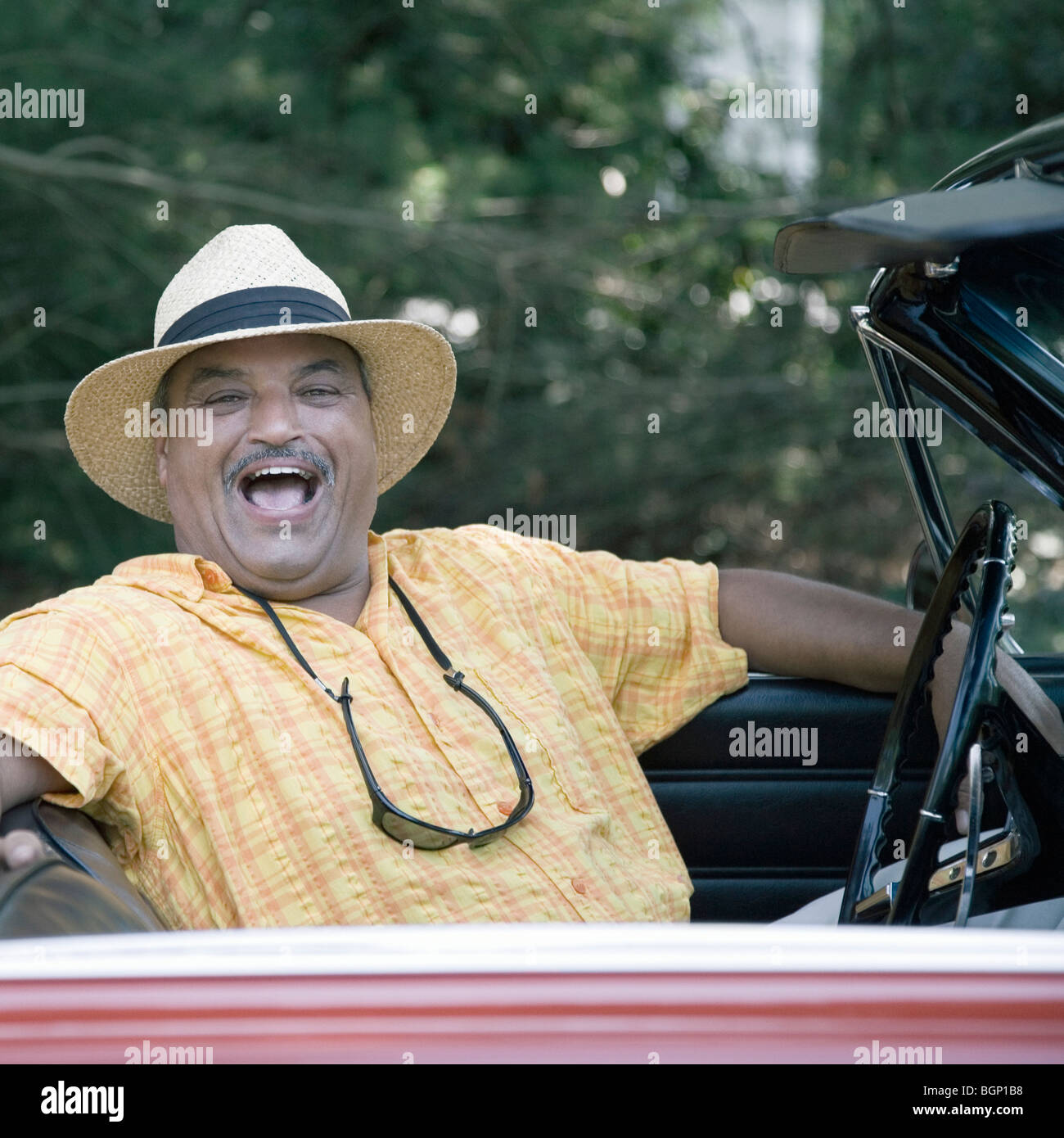 Portrait of a senior man sitting in a convertible car and laughing - Stock Image