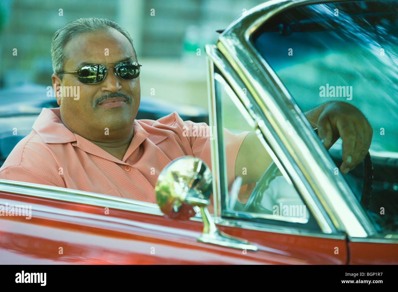Senior man driving a convertible car - Stock Image