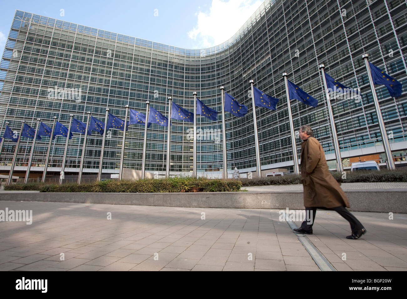A man walks next to the european flags outside the Berlaymont building, the European Commission headquarters in - Stock Image