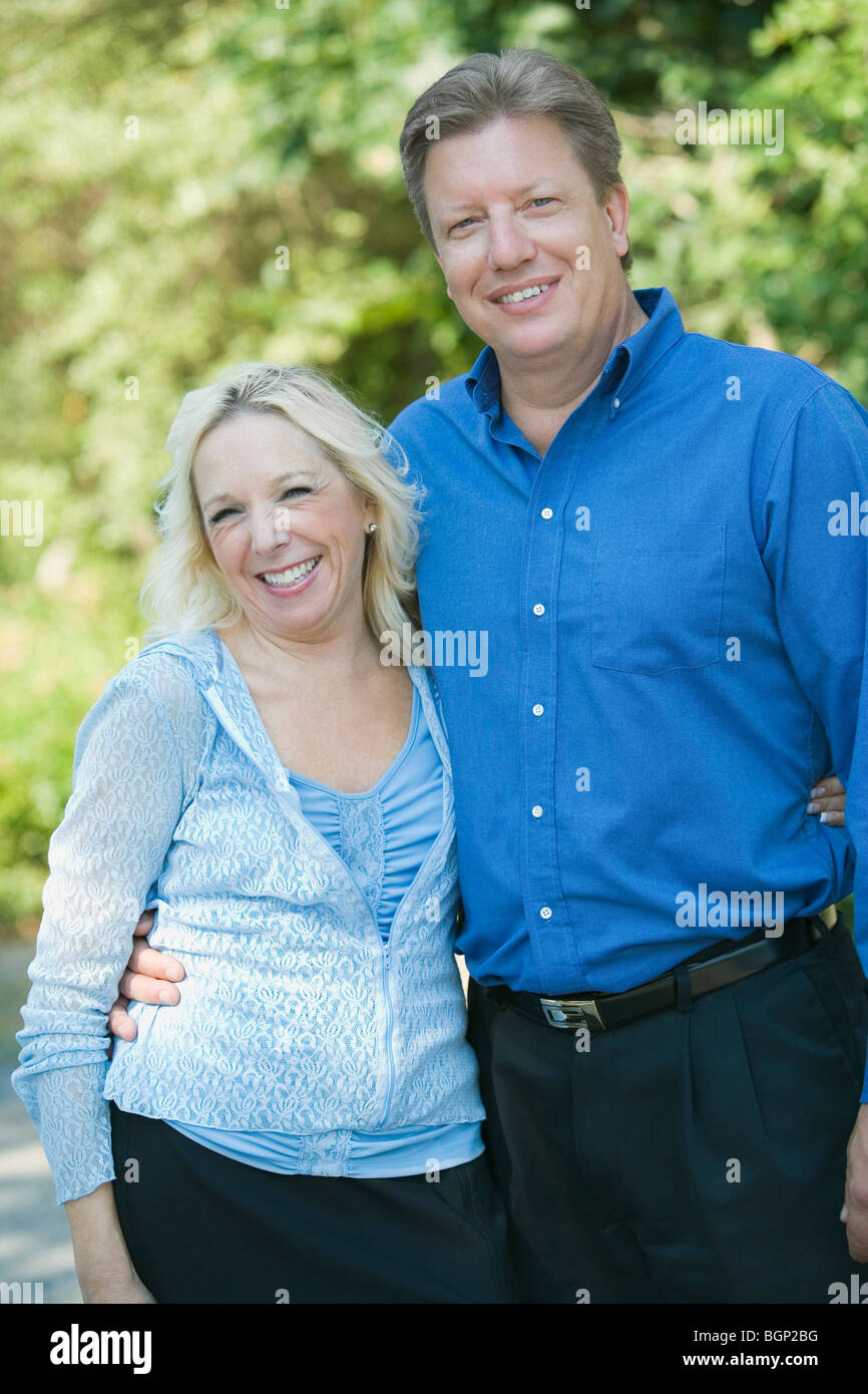 Mature couple standing with their arm around to each other and smiling - Stock Image
