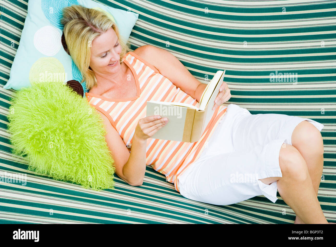 High angle view of a mid adult woman lying in a hammock and reading a book - Stock Image