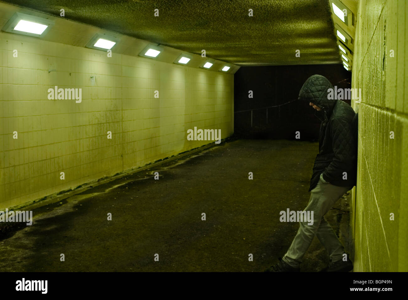 Teenage boy leaning against subway wall at night, London UK - Stock Image