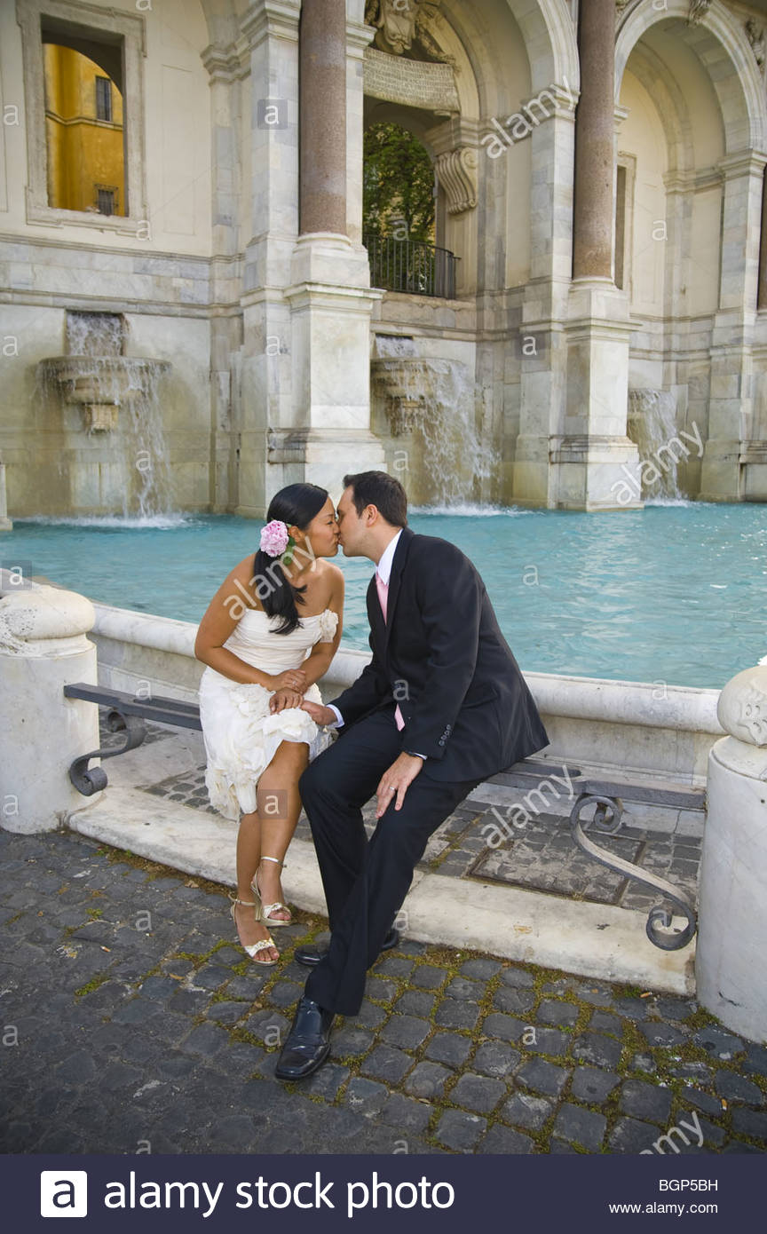 Portrait of newlyweds sitting and kissing in front of Water fountain. Fontanone dell Acqua Paola, Fontanone del - Stock Image