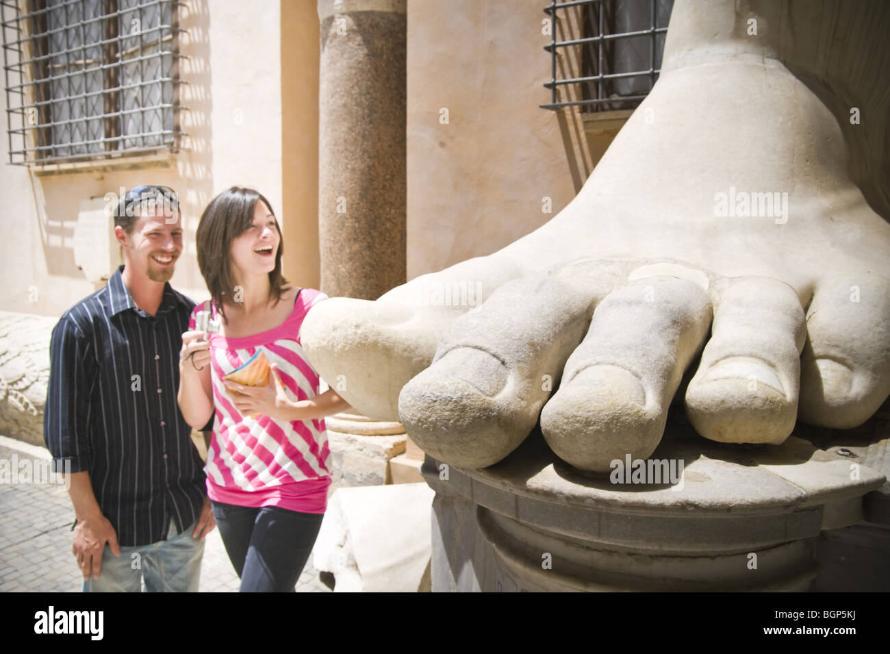 Young couple looking at large foot statue in Capitoline Museum in - Stock Image