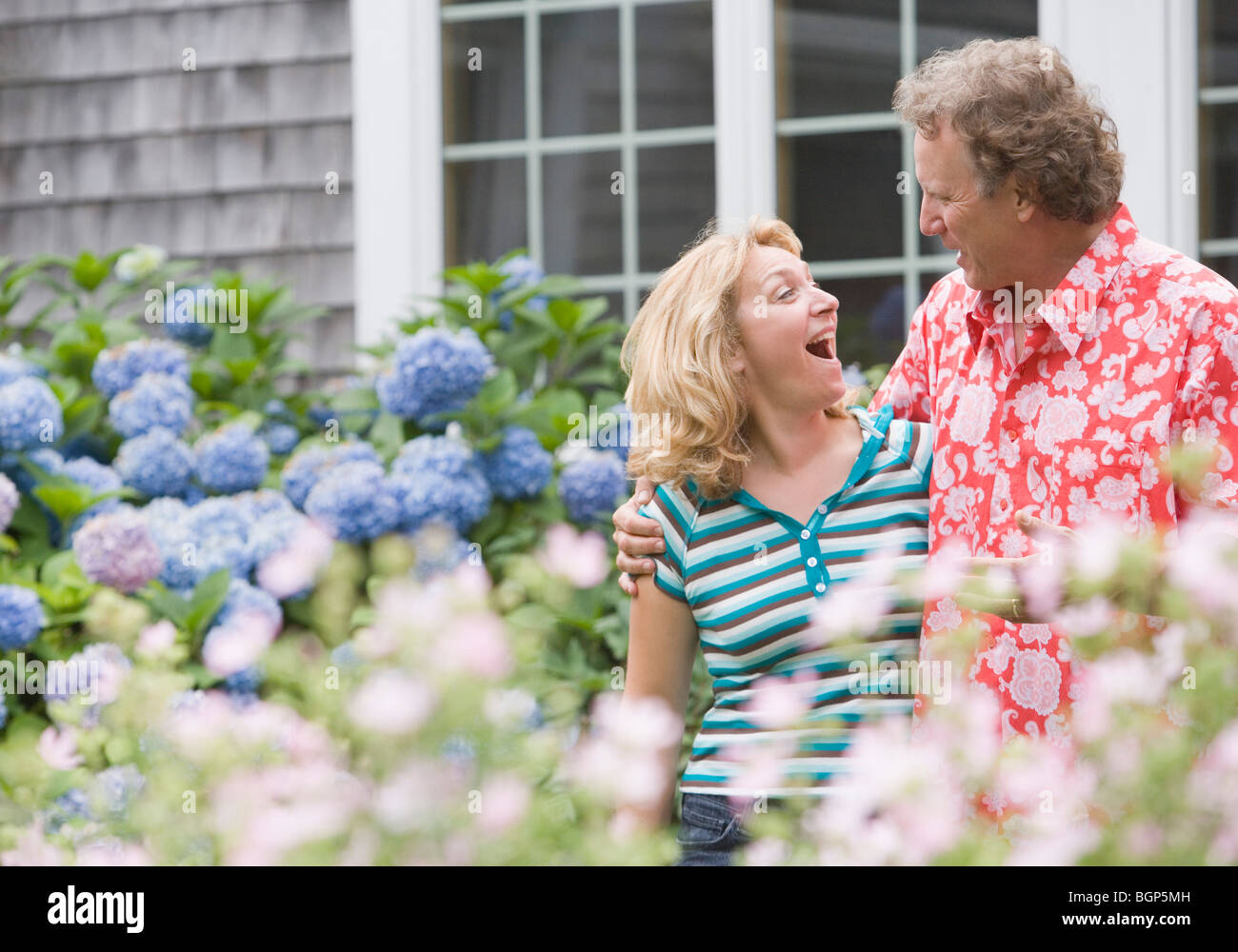 Mature man standing arm around a mature woman in a garden - Stock Image
