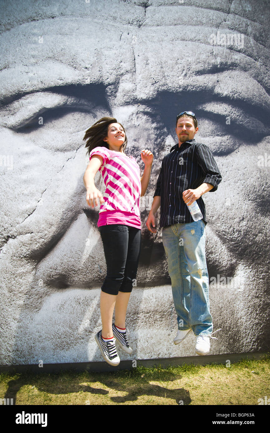 Young couple jumping in midair in front of a picture of Vespasiano in Rome, Italy - Stock Image