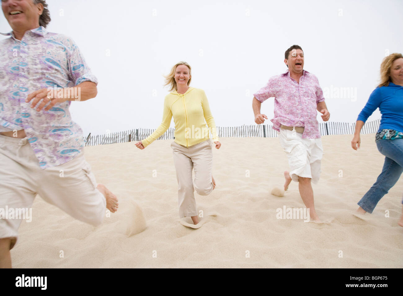 Two couples running on the beach - Stock Image