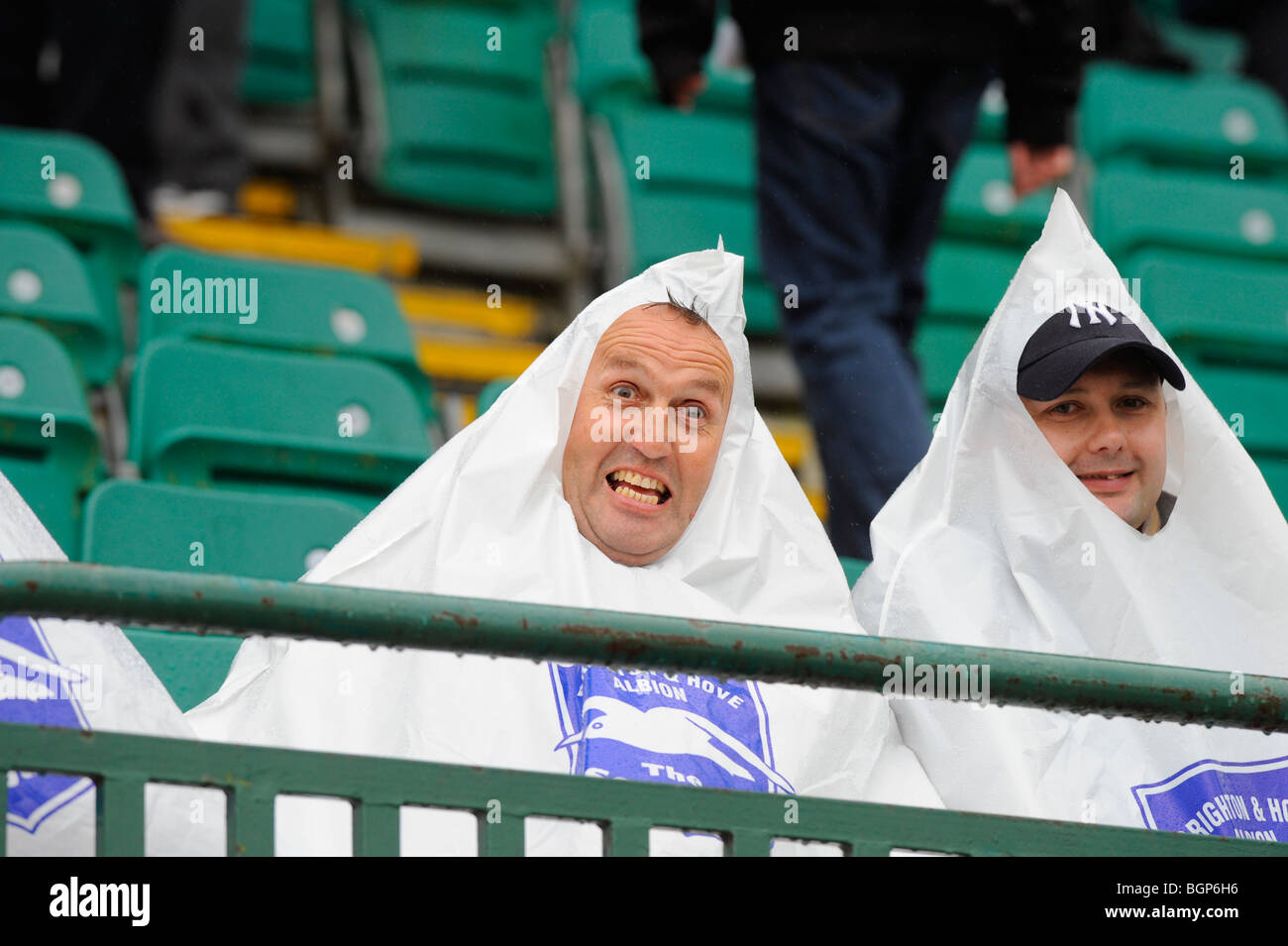 Heavy rain sees these two dedicated football supporters wearing pyramid shaped plastic bags to keep dry at Brighton. - Stock Image