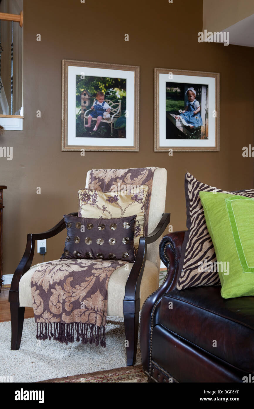 ARMCHAIR IN SITTING ROOM COVERED WITH BLANKET AND MATCHING PILLOWS. AMERICAN COUNTRY HOME - Stock Image