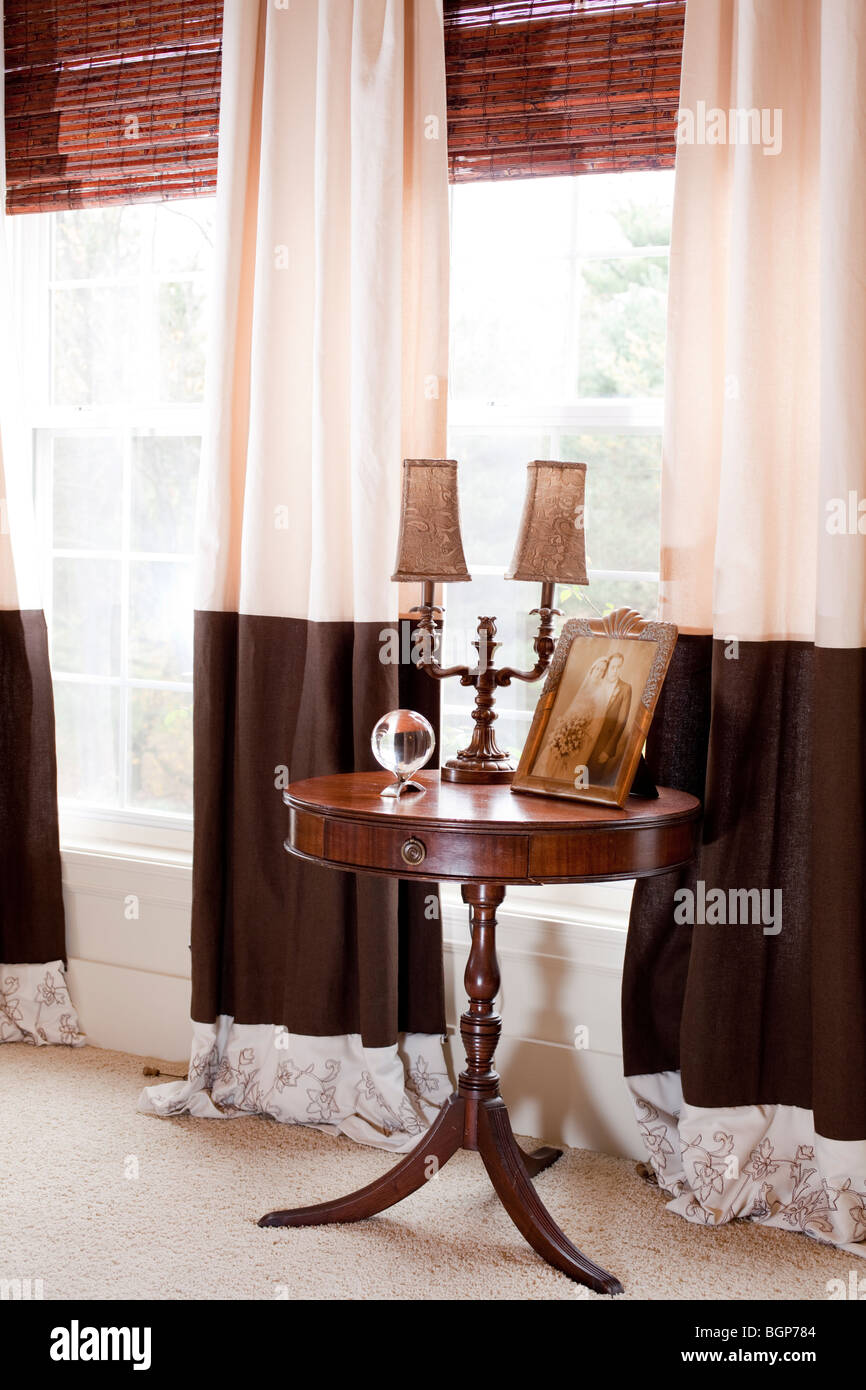 Freestanding table with drawer by the windows furnished with matching curtains in master bedroom. Details - Stock Image