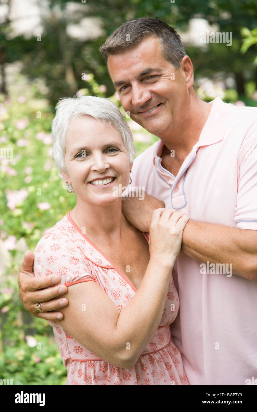 Portrait of a mature man with arm around his wife and smiling - Stock Image