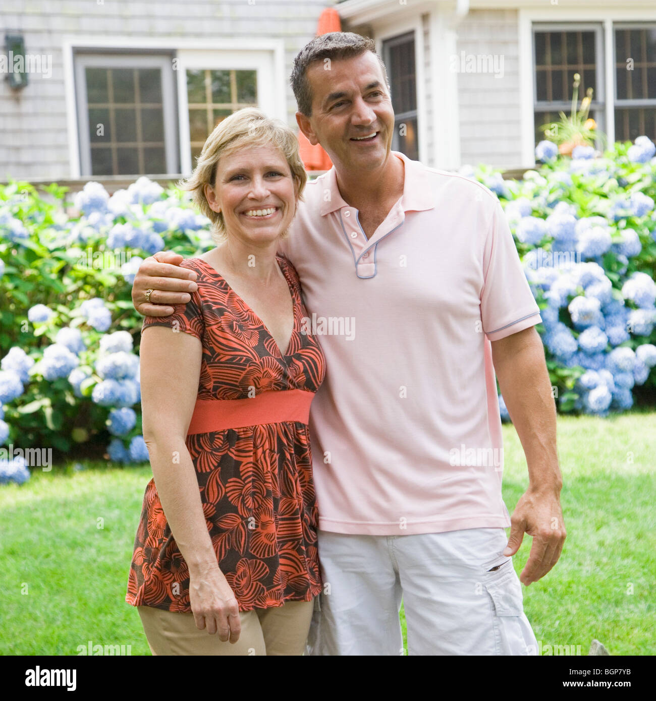 Mature couple standing in a garden with arm around - Stock Image