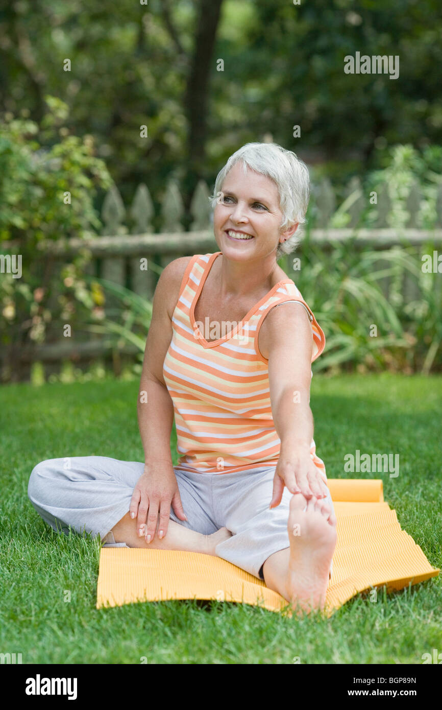 Mature woman exercising in a park - Stock Image