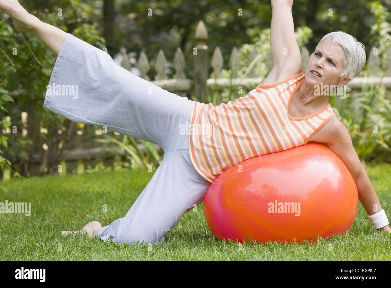 Mature woman exercising with a fitness ball - Stock Image