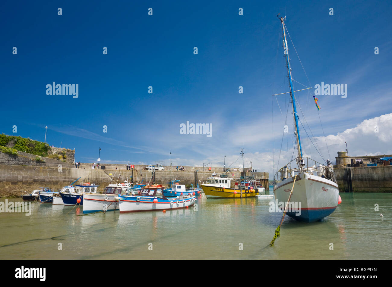 Small fishing boats and a yacht at low tide Newquay harbour Newquay Cornwall England GB UK EU Europe - Stock Image