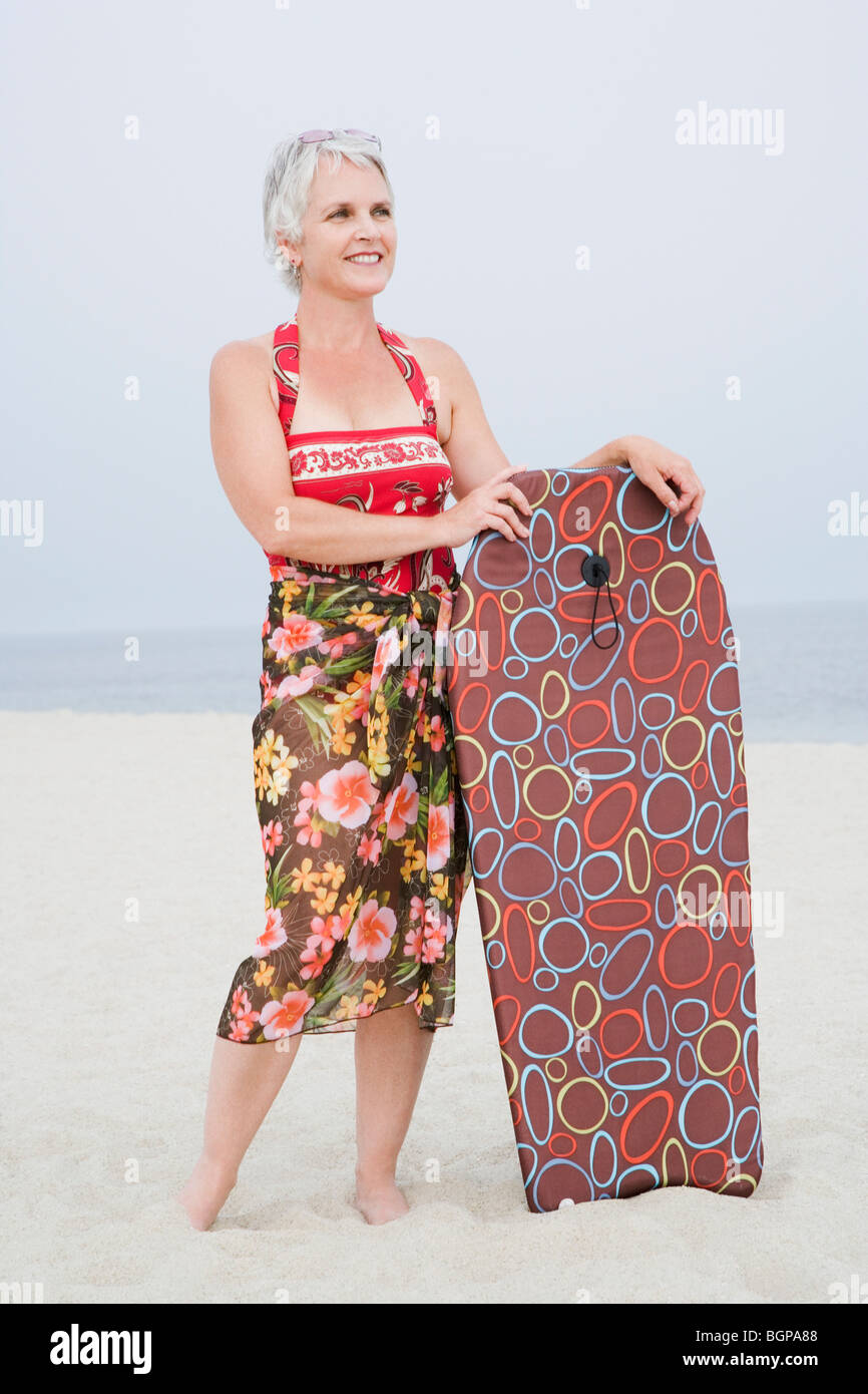 Mature woman holding a body board on the beach - Stock Image