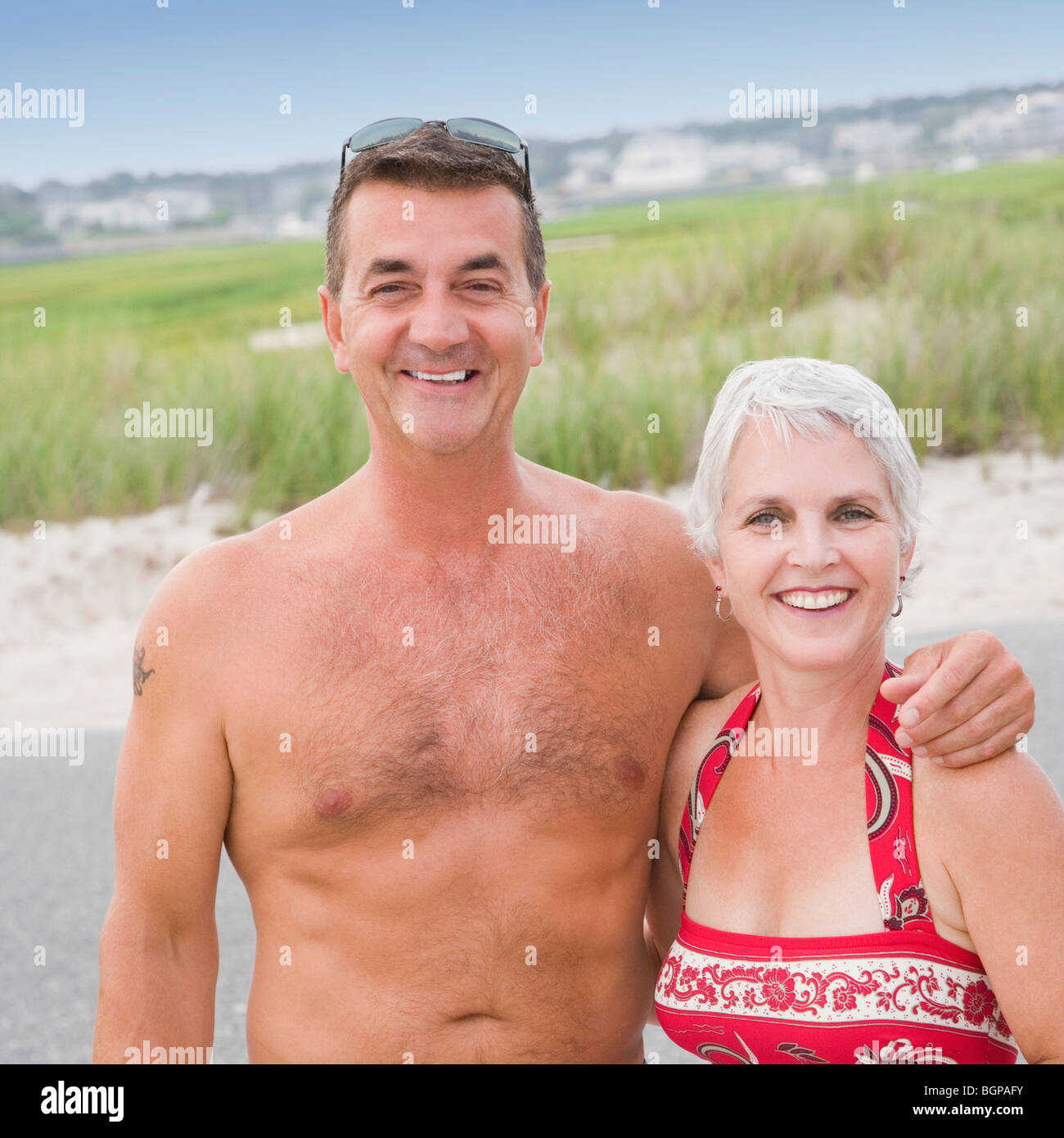 Portrait of a mature couple smiling with arm around - Stock Image