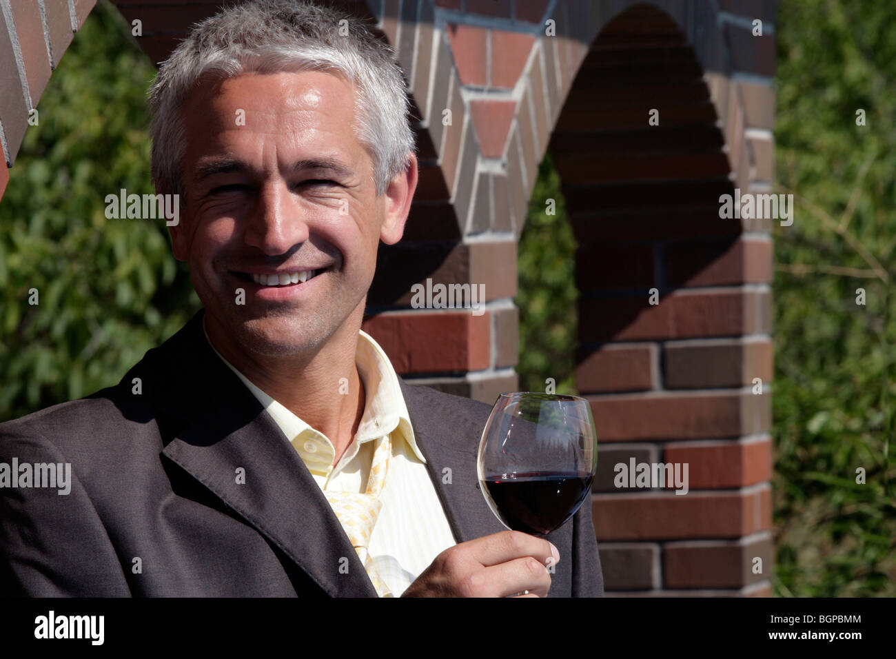 Wine maker holding glass of red wine standing before brick wall in his vineyard - Stock Image