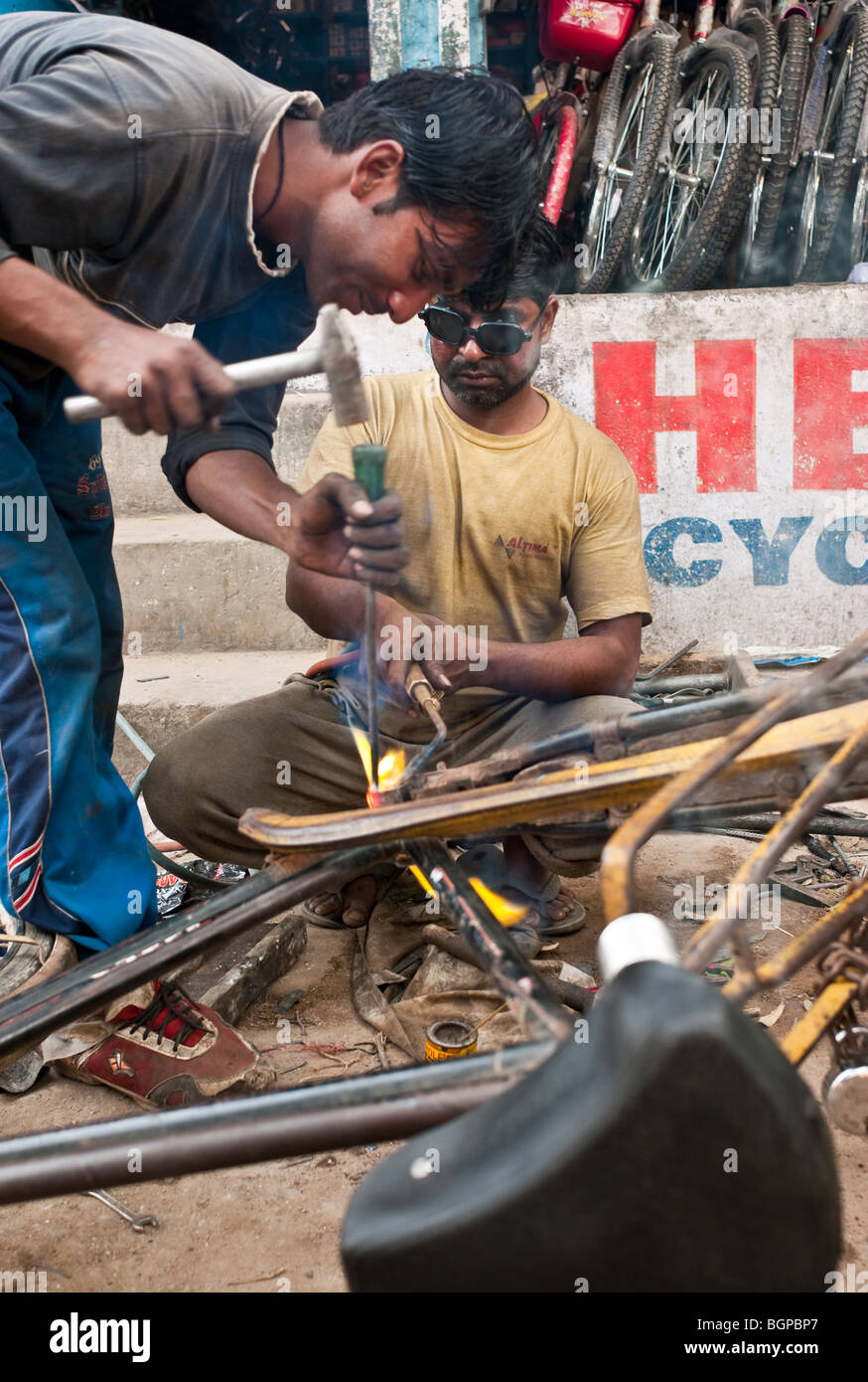Mechanics welding a bicycle in the backstreet on Delhi, India - Stock Image