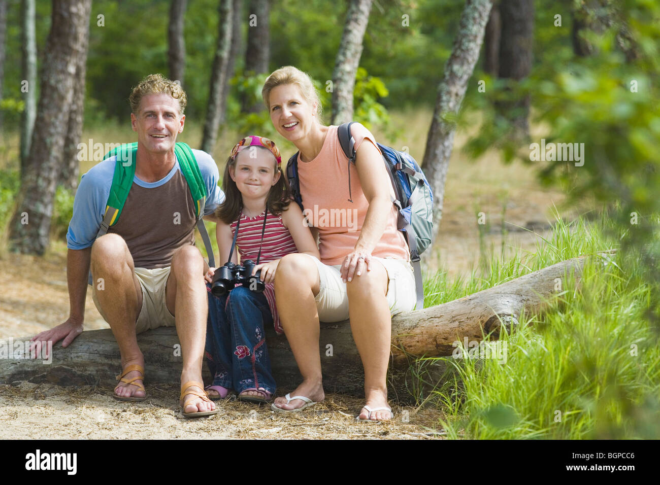 Portrait of a mature couple sitting on a tree trunk with their daughter in a forest Stock Photo