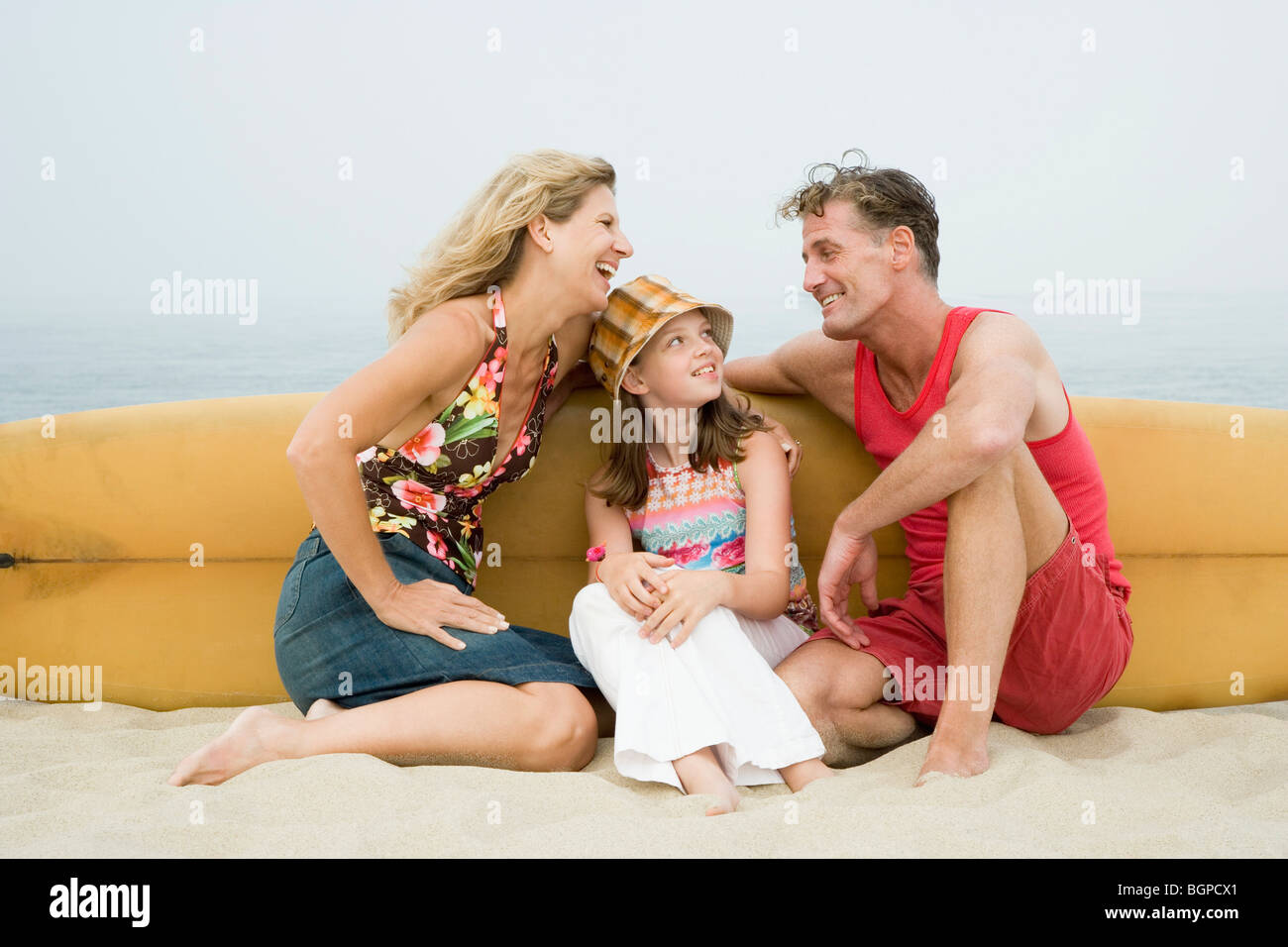 Mature couple and their daughter sitting on the beach with a surfboard Stock Photo