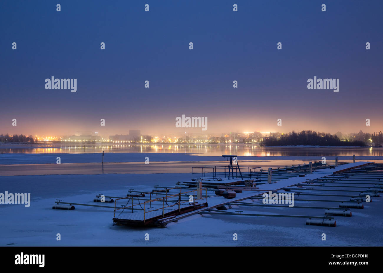 Small boat harbour at Wintertime. Empty pier at river Oulujoki. City of Oulu at the background , Finland - Stock Image