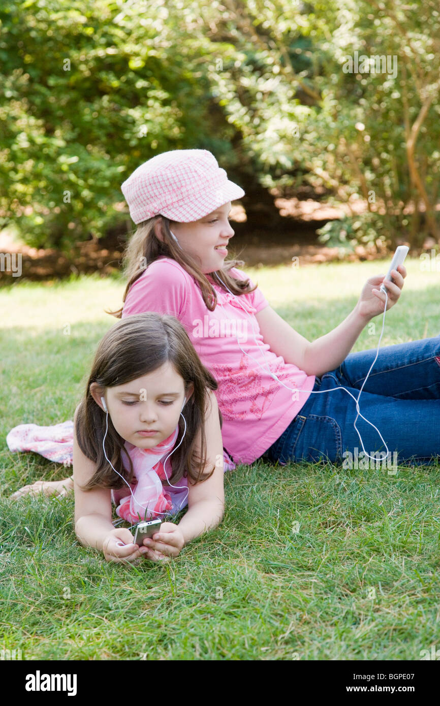 Two sisters listening to MP3 players in a park - Stock Image