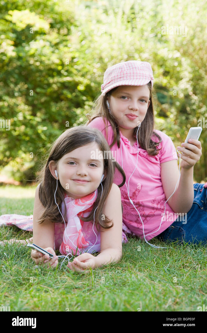 Portrait of two sisters listening to MP3 players in a park - Stock Image