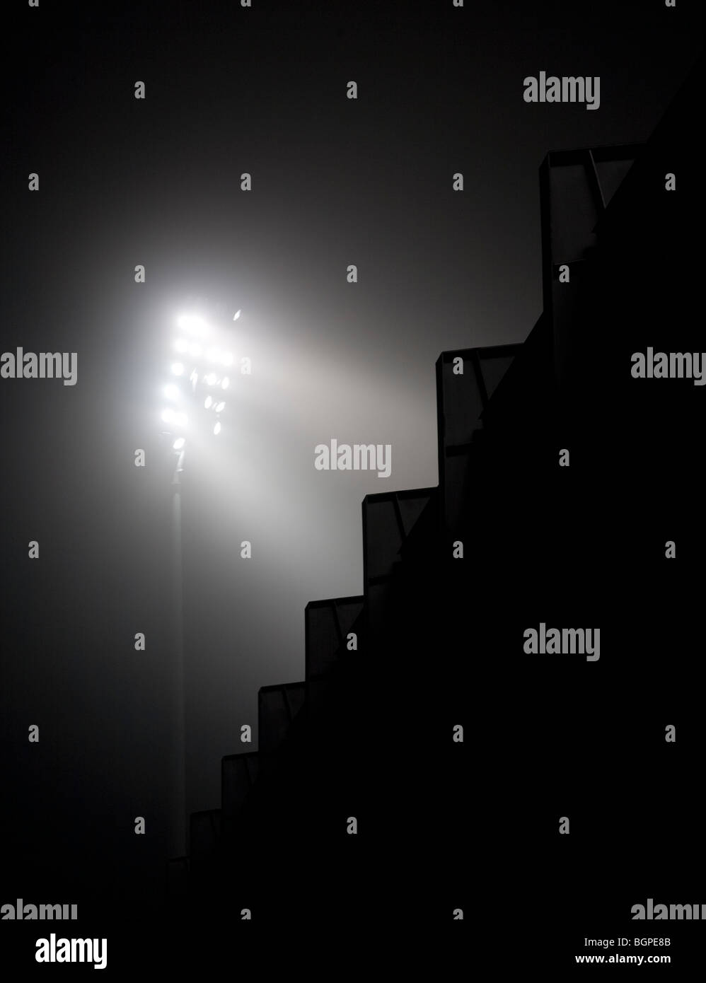 Stadium lights glowing through fog at night . Jagged edge of the stand at darkness . - Stock Image