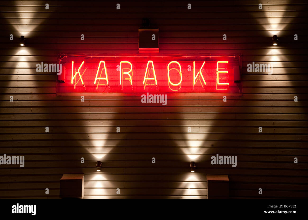 Red Karaoke neon sign on wall - Stock Image