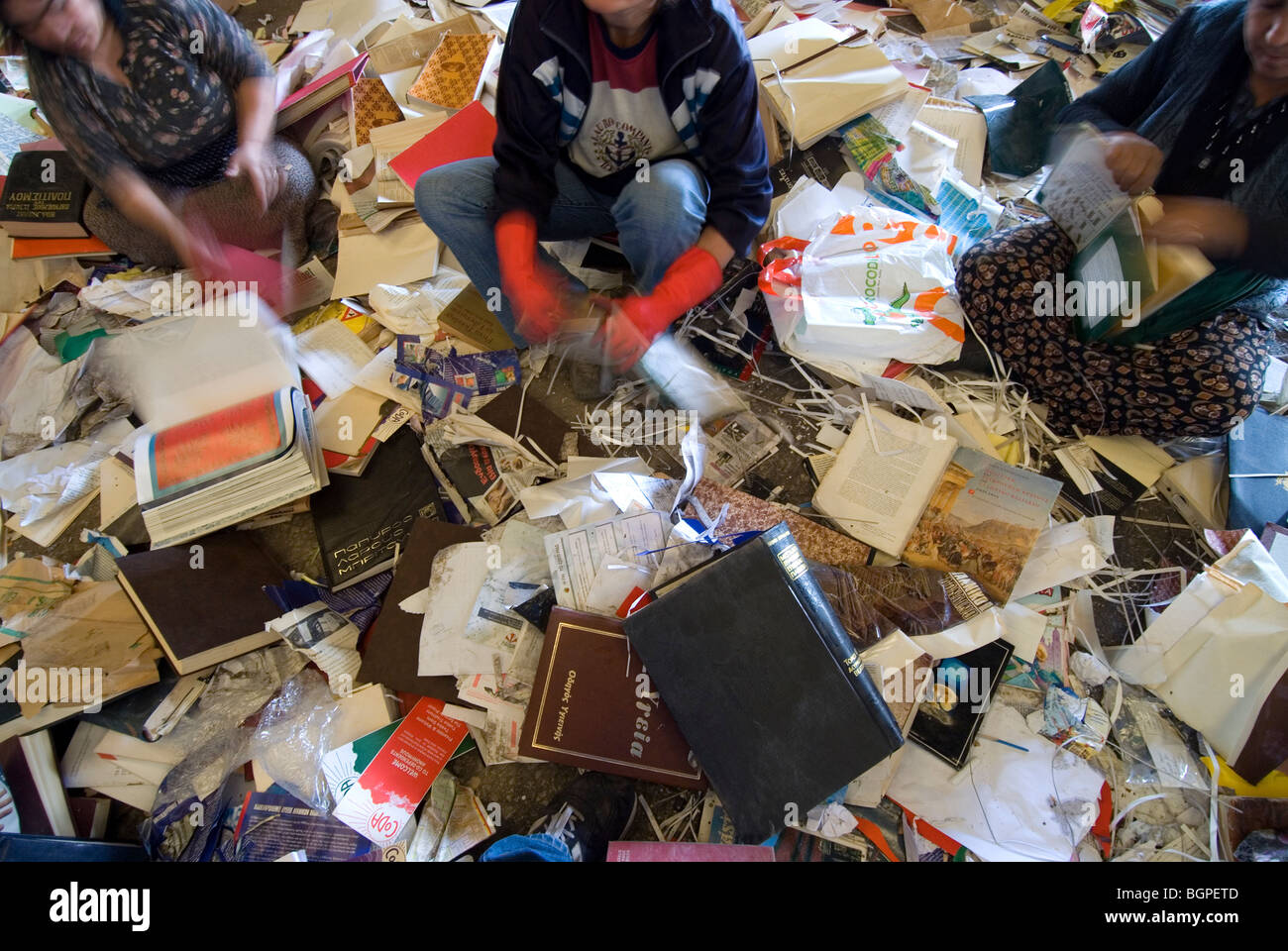Women sorting manually different types of waste paper before the recycling process Stock Photo